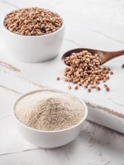 Buckwheat flour and buckwheat on white background