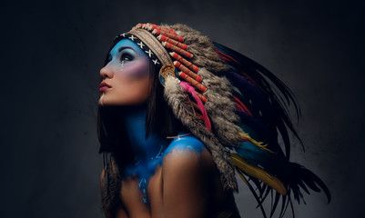 Female with Indian feather hat and colorful makeup.