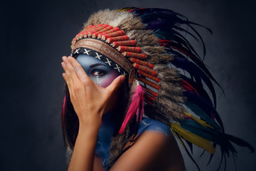 Foto op Plexiglas Body Paint Female with Indian feather hat and colorful makeup.