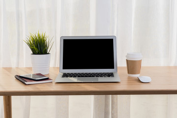 Laptop with smart phone notebook and coffee cup on workplace table.