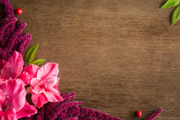 Chains of small, purple flowers with pink gladiolus flower on the brown wooden table. Greeting card or web background. Empty place for a text. Top view.