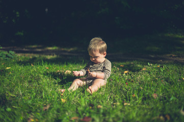 Little baby playing on the grass outside