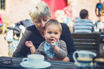 Baby with grandmother at table outside