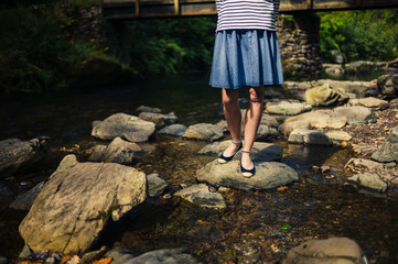 Woman in skirt standing on rocks in river