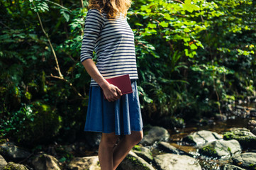 Young woman with book in river