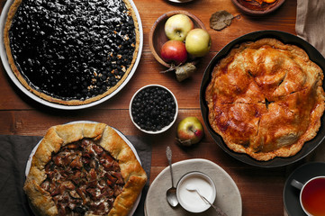 Traditional autumn pies arranged on red wooden rustic table. Chanterelle mushrooms, blueberry and sweet apple fillings. Top view.