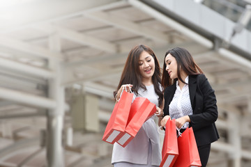 Asian women with red shopping bags