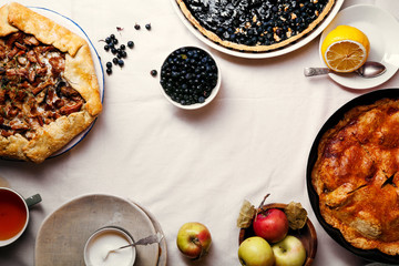 Traditional autumn pies arranged on white linen fabric. Chanterelle mushrooms, blueberry and sweet apple fillings. Top view, copy space.