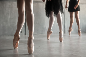 Close-up of the legs of three young  ballerinas in white pantyhose, black packs and pointes performing a dance in a dark studio. Russian ballet in details