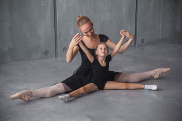 A beautiful adult blonde Russian ballerina in a black tutu and white pantyhose holds her hands up, sits on a string and teaches a charming little blonde how to properly dance a Russian ballet
