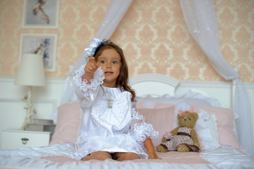 Little girl in the nursery on a bed with teddy bear.