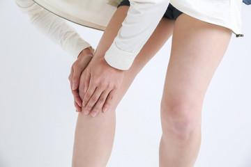 膝を触る女性
