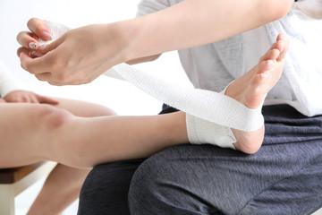 足に包帯を巻く女性