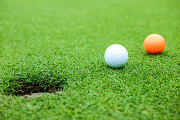 White and orange color golf ball on green near hole at the morning time