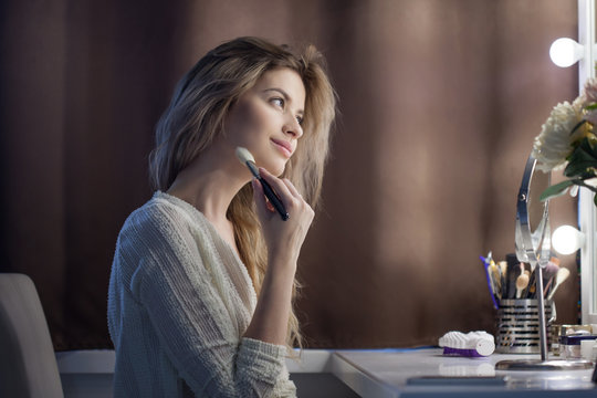 Amazing young woman doing her makeup in front of mirror. Portrait of beautiful girl near cosmetic table
