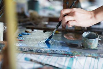 Artist mixes oil paints on pallet
