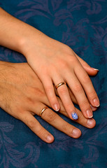 Photo of hands with beautiful wedding rings on blue background