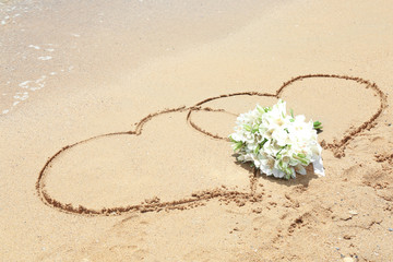Beautiful bouquet and drawing of hearts on sand. Beach wedding concept