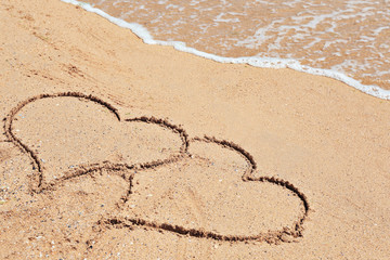 Drawing of hearts on sand. Beach wedding concept