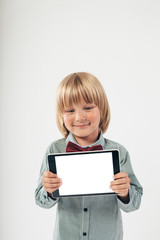 Smiling School boy in shirt with red bow tie, holding tablet computer in white background