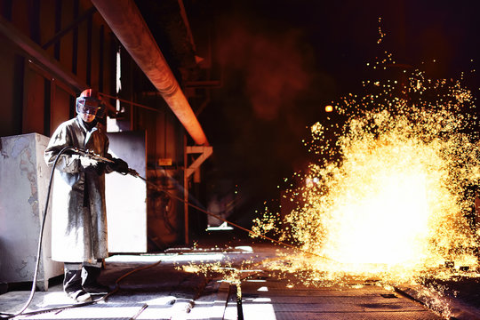 A man working at a metallurgical plant against a blast furnace, molten metal, and sparks
