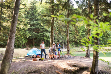 Spoed Foto op Canvas Kamperen Beautiful family camping in forest, eating together.