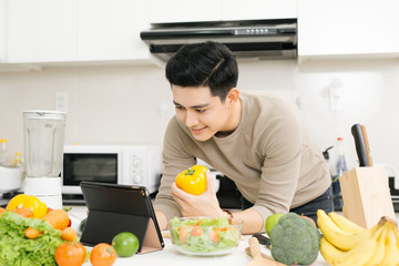 Young asian handsome man preparing food in kitchen at home