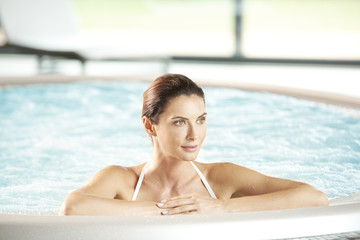 Beautiful woman relaxing in jacuzzi at the spa.