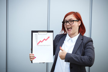 Business concept of success and growth. A successful woman boss, in suit and wearing glasses, holds a tablet with charts of growth and achievements. With place for text. Chef Day, Boss Day