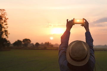 Tourist woman taking photo with smartphone on sunset nature background