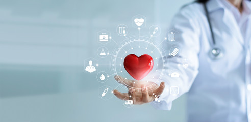 Medicine doctor holding red heart shape iwith medical icon network connection modern virtual screen interface, service mind and medical technology network concept