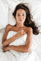 Top view of a sensual young asian woman lying in bed