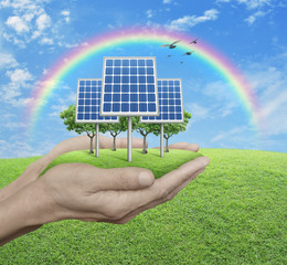 Solar cell in man hands over green grass with blue sky, clouds, and rainbow, Ecological concept