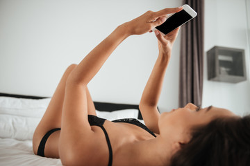 Alluring sexy asian woman in lingerie taking a selfie