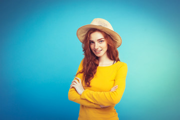 Travel concept - Close up Portrait young beautiful attractive redhair girl wtih trendy hat and sunglass smiling. Blue Pastel Background. Copy space.