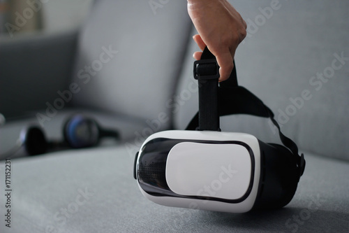 0f9481ee4be0 Man holding virtual reality goggles on sofa in living room background