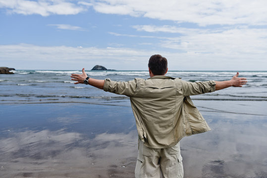 Happy man with raised hands near the ocean. New Zealand landscape