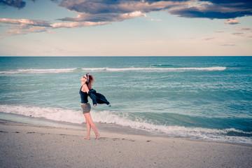 Femme sur la plage au coucher du soleil