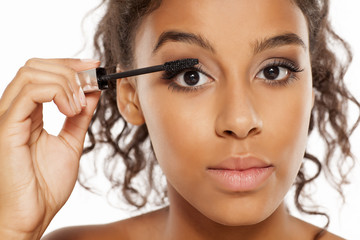 a young dark skinned woman applying a mascara to her eyelashes