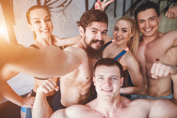 Group of sportive people in a gym taking selfie