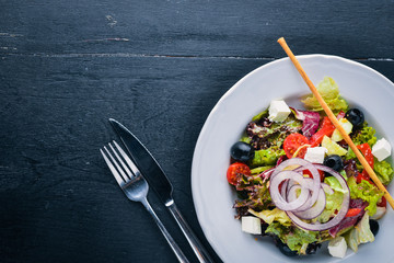Greek salad. Fresh vegetables on a wooden background. Top view. Free space for text.