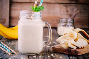 banana smoothie with oat flakes in mason jar on a wooden background