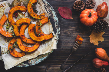 Baked pumpkin and autumn decoration on the wooden table, top view