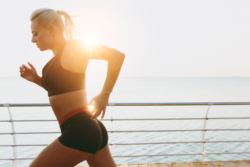 Young beautiful athletic girl with long blond hair in headphones listening to music and running at sunrise over the sea