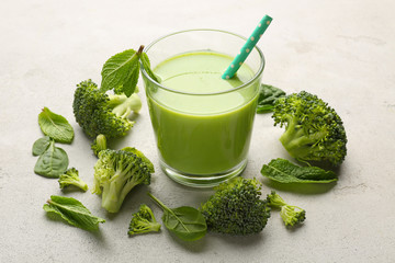 Glass with fresh green juice and ingredients on table