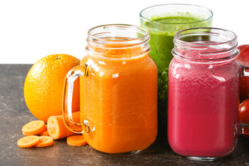 Mason jars with fresh juices and ingredients on table