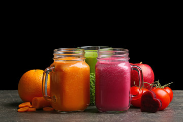 Mason jars with fresh juices and ingredients on table against black background