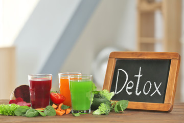 Small chalkboard with word DETOX, fresh juices in glasses and ingredients on table