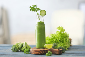 Glass bottle with fresh green juice and ingredients on table