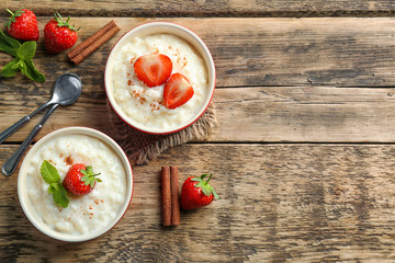 Creamy rice pudding with strawberry on wooden table